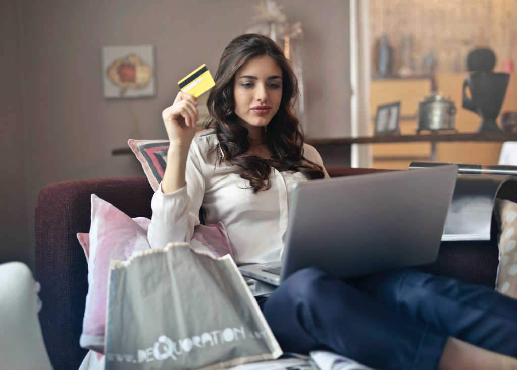 Woman holding card while shopping online